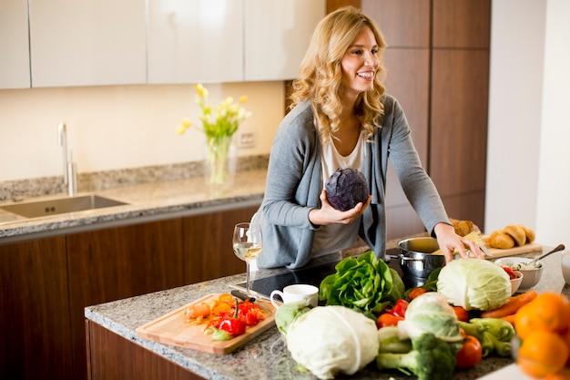 Mulher jovem, preparando alimento, em, modernos, cozinha