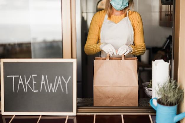 Mulher jovem preparando comida para levar dentro do restaurante durante o surto de coronavirus - foco nas mãos