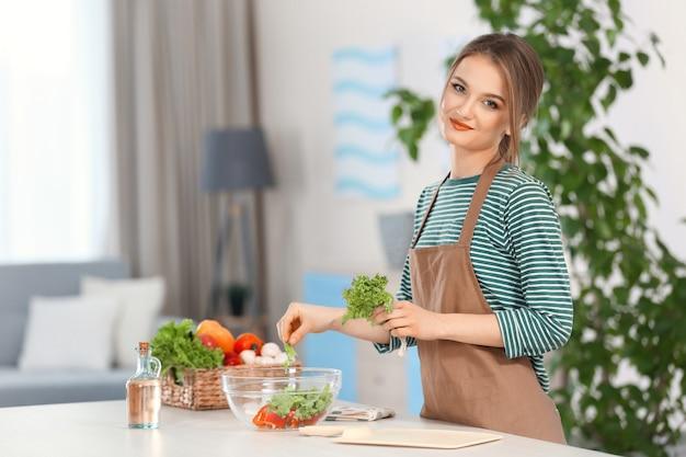 Mulher jovem preparando salada de legumes na cozinha