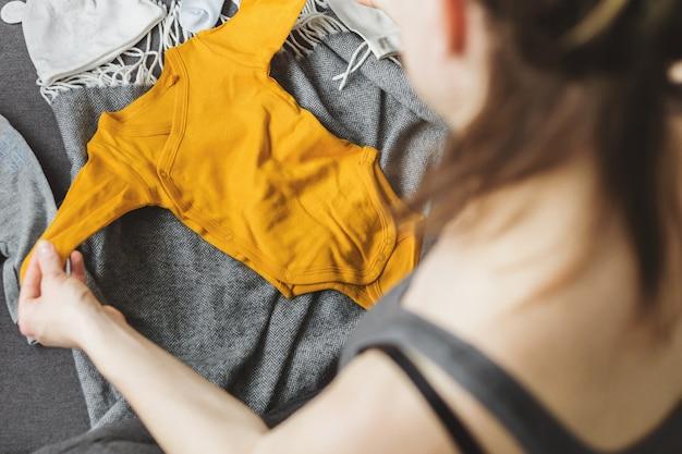 Mulher jovem, preparar, roupas, para, bebê