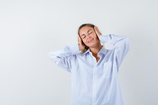 Mulher jovem pressionando as mãos nas orelhas, mantendo os olhos fechados, usando uma camisa branca e parecendo feliz