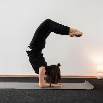 Mulher jovem profissional faz parada de mãos e mantém o equilíbrio em um estúdio de fitness. garota faz exercícios em pose de ioga.