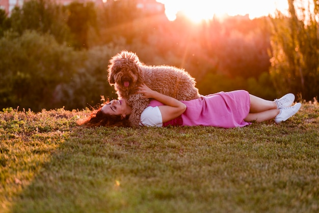 Mulher jovem proprietário com seu cão de água marrom marrom se divertindo ao ar livre em um parque ao pôr do sol. amor pelo conceito de animais