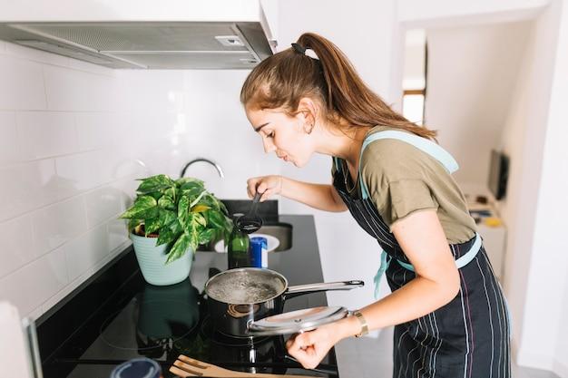 Mulher jovem, provando, a, sopa, cozinha