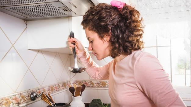 Mulher jovem, provando, sopa, de, um, concha