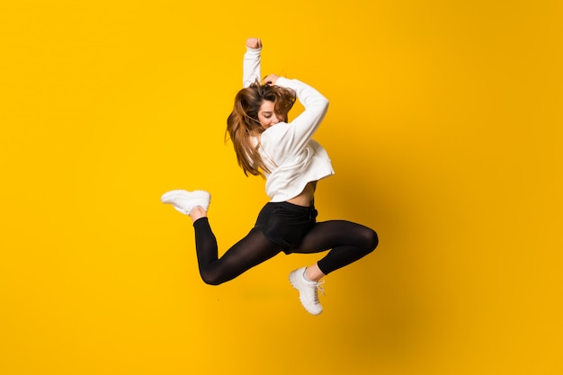 Mulher jovem, pular, isolado, parede amarela