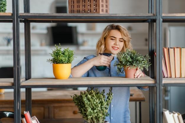 Mulher jovem pulveriza plantas caseiras na prateleira da sala de estar, passatempo da florista. fe