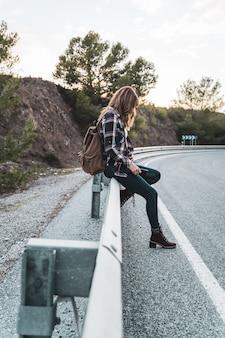 Mulher jovem quadril com sua mochila pedindo carona na estrada, à espera de um carro. conceito de exploração e aventuras.