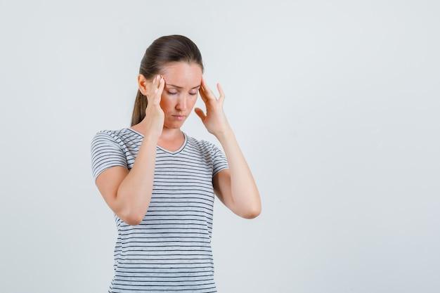 Mulher jovem que sofre de dor de cabeça em t-shirt, vista frontal.