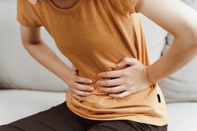 Mulher jovem que sofre de fortes dores abdominais, sentada no sofá em casa. gastrite, período menstrual.