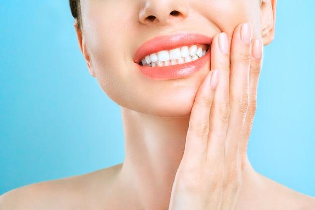 Mulher jovem que sofre de fortes dores nos dentes, tocando sua bochecha com a mão.