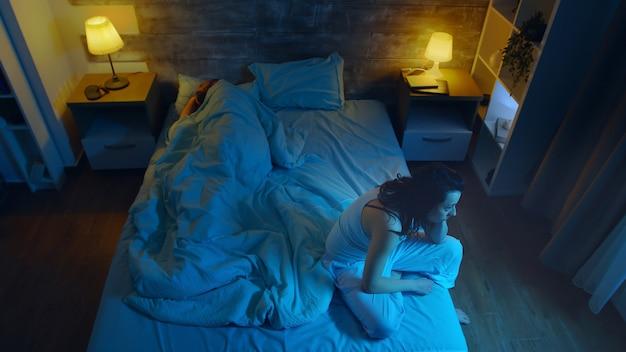 Mulher jovem que sofre de insônia enquanto o marido dorme. sala com luz da lua.