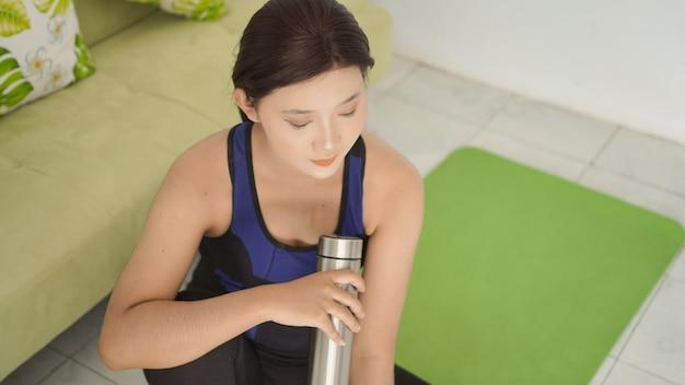 Mulher jovem que terminou de ioga está descansando em casa