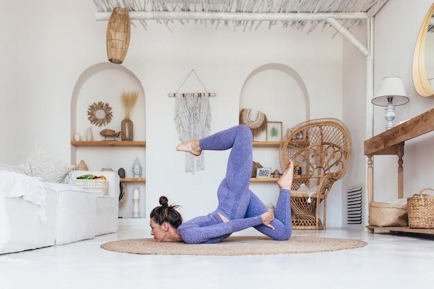 Mulher jovem que trabalha em casa fazendo exercícios de ioga avançados.