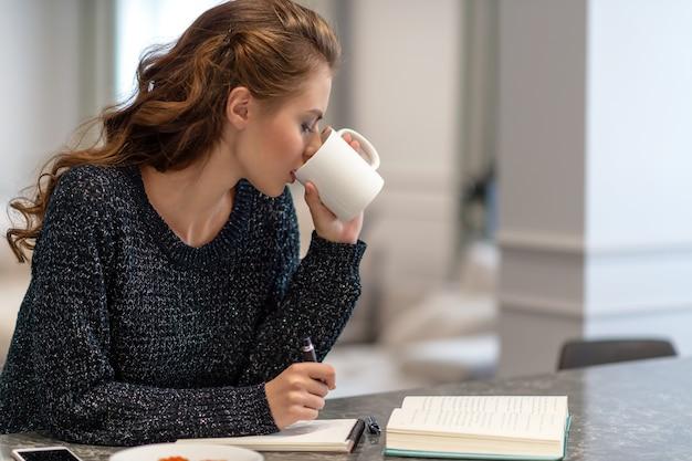 Mulher jovem que trabalha em casa usando o bloco de notas na cozinha. ela está bebendo café. idéias para negócios. estudar e trabalhar em casa.