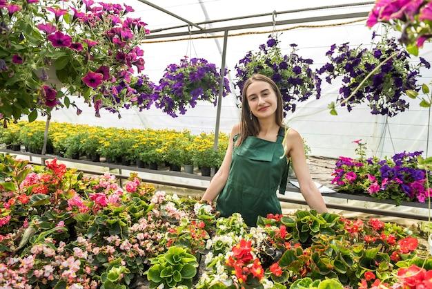 Mulher jovem que trabalha em uma estufa, cuidando de flores.