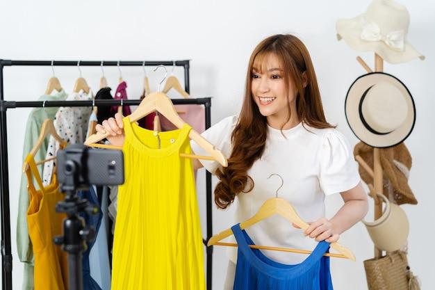 Mulher jovem que vende roupas e acessórios on-line por streaming ao vivo em smartphone, e-commerce empresarial on-line em casa