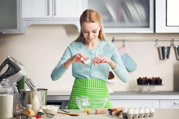 Mulher jovem quebrando um ovo em uma tigela