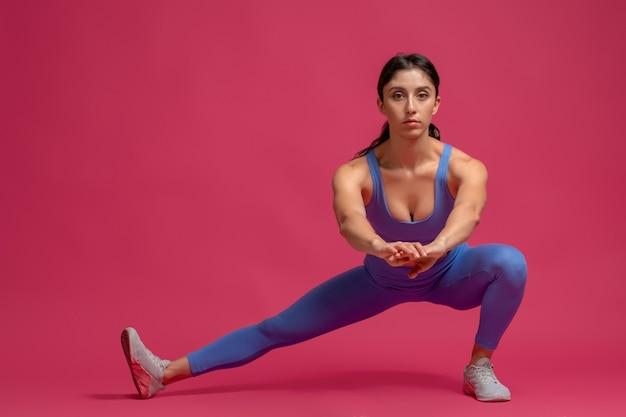 Mulher jovem realizando estocadas laterais com peso corporal