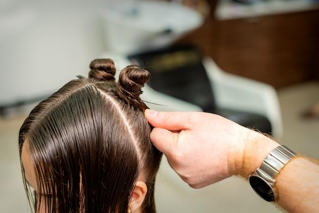 Mulher jovem recebe processo de penteado por cabeleireiro em salão de beleza