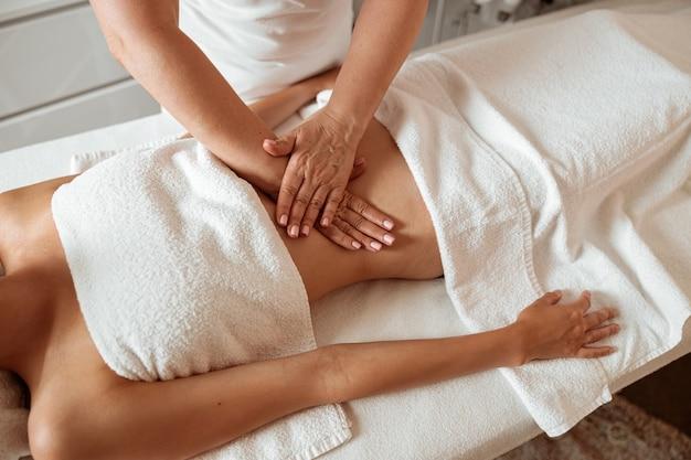 Mulher jovem recebendo massagem abdominal em salão de spa