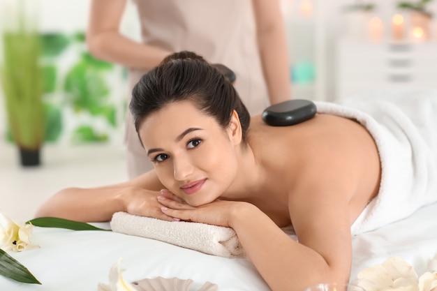 Mulher jovem recebendo massagem com pedras quentes em salão de spa