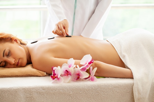 Mulher jovem, recebendo massagem com pedras quentes no salão spa.