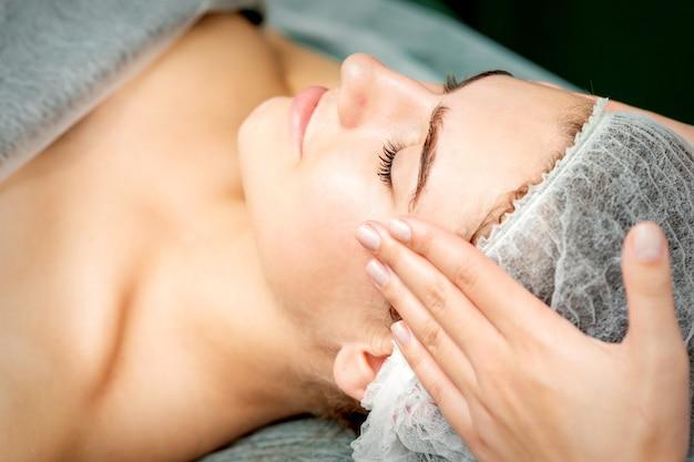 Mulher jovem recebendo massagem facial com os olhos fechados por esteticista em salão de beleza