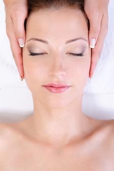 Mulher jovem recebendo massagem facial em salão de spa