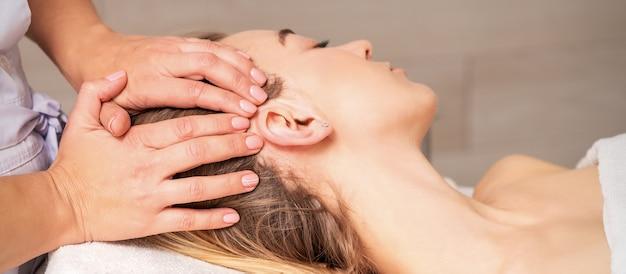 Mulher jovem recebendo massagem na cabeça pelas mãos da esteticista no centro de beleza do spa