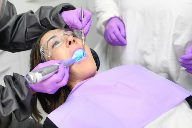 Mulher jovem recebendo procedimento de luz ultravioleta no consultório dentista