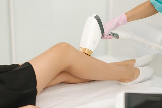 Mulher jovem, recebendo tratamento a laser na perna no spa. depilação a laser e cosmetologia