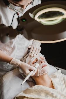 Mulher jovem recebendo tratamento com máscara de pele