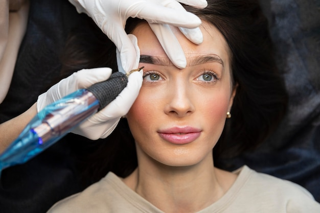 Mulher jovem recebendo tratamento de beleza para as sobrancelhas