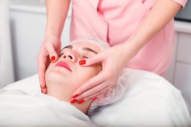 Mulher jovem, recebendo tratamento de spa no salão de beleza. terapia de spa. massagem facial. tratamento facial. cuidados com a pele e o corpo.
