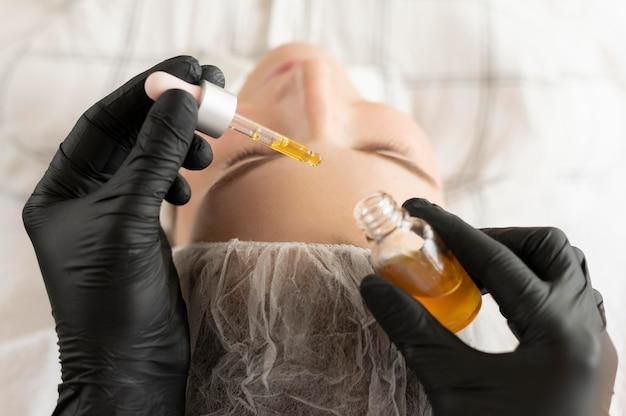 Mulher jovem recebendo tratamento para sobrancelha no salão de beleza