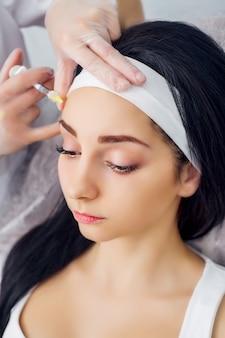 Mulher jovem recebendo uma injeção de ácido hialurônico