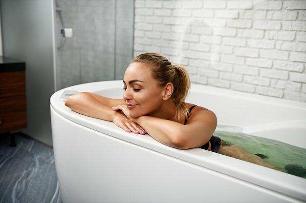 Mulher jovem relaxa com os olhos fechados enquanto recebe procedimentos de bem-estar na cápsula de bem-estar do spa.