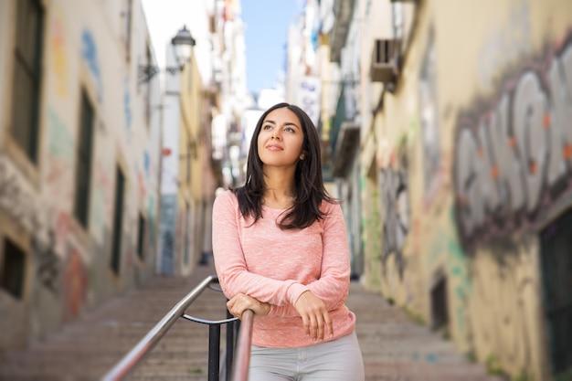 Mulher jovem relaxada, apoiando-se na grade de escadas da cidade