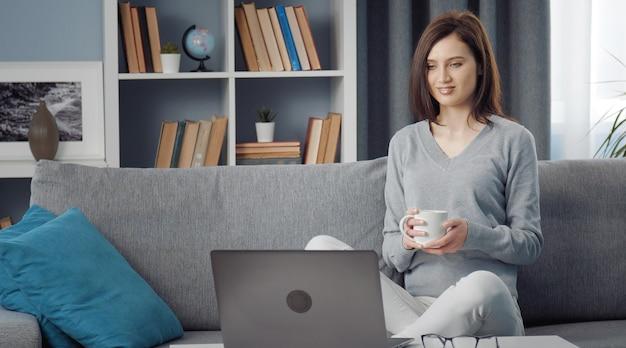 Mulher jovem relaxada sentada no sofá segurando uma xícara e olhando para a tela do laptop na sala de estar