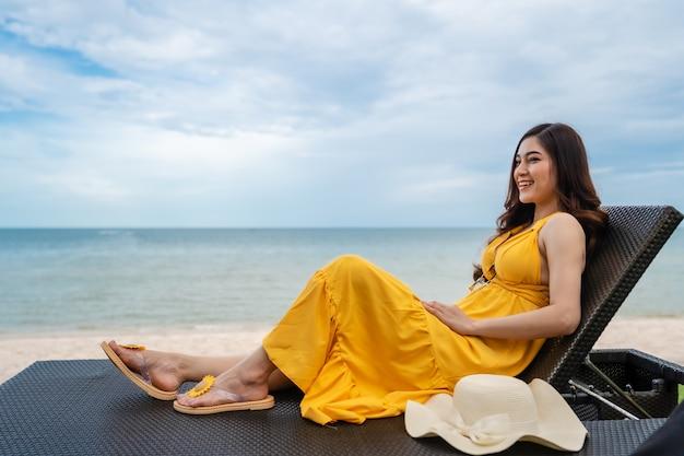 Mulher jovem relaxando em uma cadeira na praia de hua hin, tailândia
