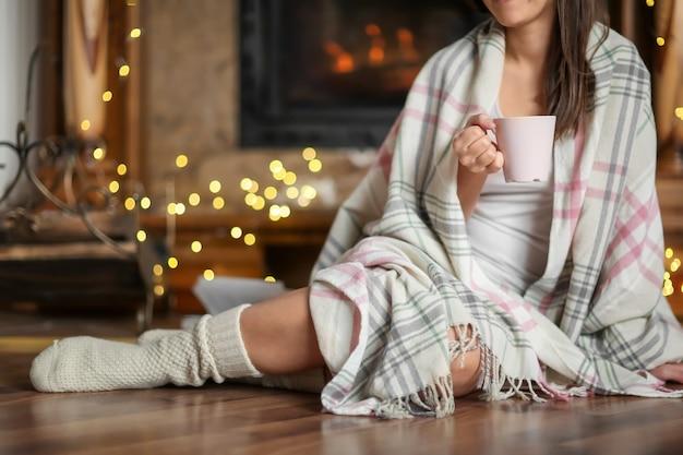 Mulher jovem relaxando enquanto bebe chá na sala de estar decorada para as férias de inverno