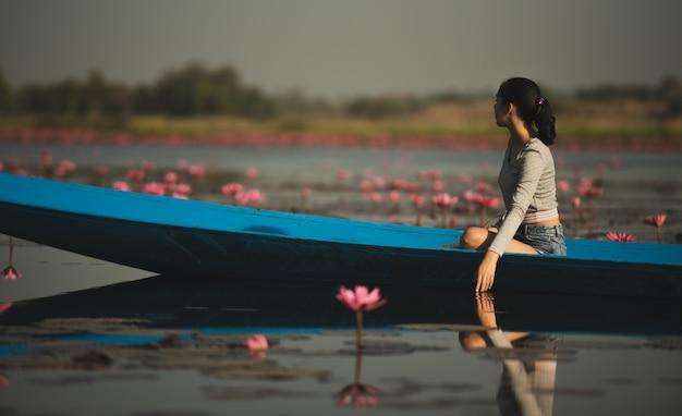 Mulher jovem, relaxante, com, bonito, flor lotus, campo, em, a, vermelho, mar loto