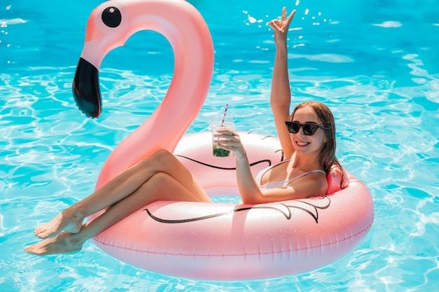 Mulher jovem, relaxante, em, flamingo, anel nadador