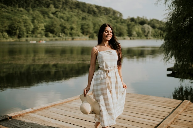 Mulher jovem relaxante em um píer de madeira no lago calmo