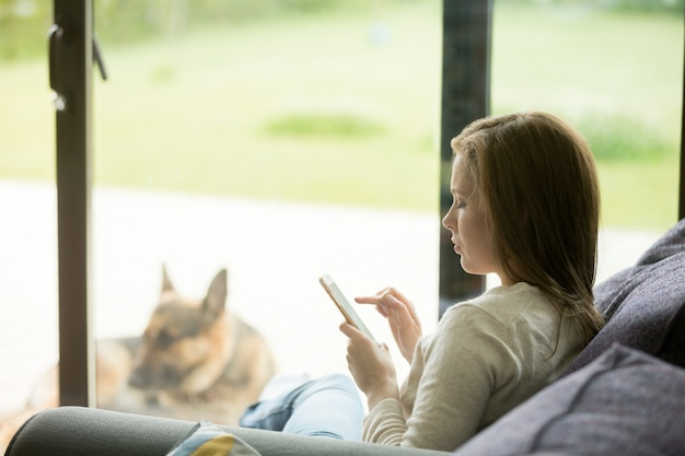 Mulher jovem, relaxante, sofá, usando, smartphone, apps, dentro, casa