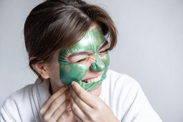 Mulher jovem remove a máscara verde do rosto, máscara de colágeno para pele facial, procedimento de spa.