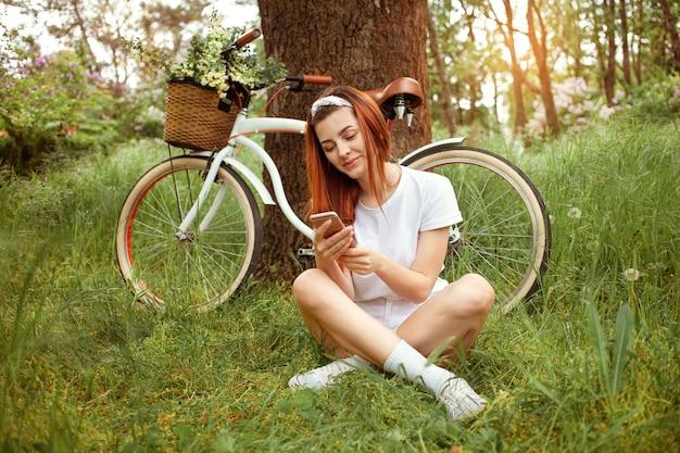 Mulher jovem repousa na natureza. uma garota se senta na grama com seu telefone. bicicleta para alugar e alugar durante o dia. verão primavera. tecnologia, internet para se comunicar com amigos nas férias, redes sociais
