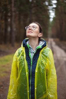 Mulher jovem respira ar puro na floresta depois da chuva, descansa, relaxa, em pé com uma capa de chuva amarela, respira com os olhos fechados
