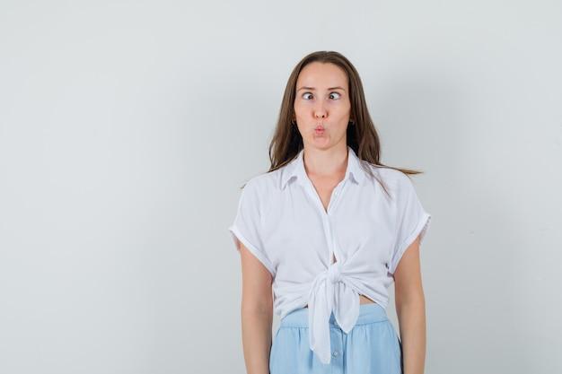 Mulher jovem revirando os olhos em uma blusa branca e saia azul claro e parecendo divertida